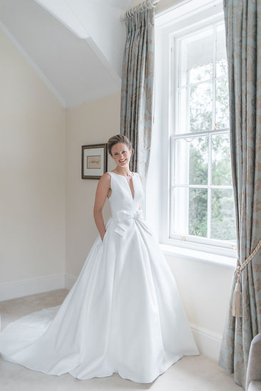 Smiling bride standing by window in Jesus Peiro wedding dress from Miss Bush Bridal