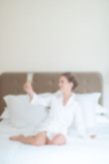 Bride with champagne glass cheers on bed in white silk dressing gowns English wedding