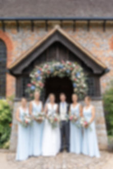 Bride and groom with bridemaids standing under flower arch at traditional English church wearing Jesus Peiro