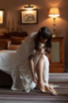 Bride putting on Gucci heels luxury London wedding photographer