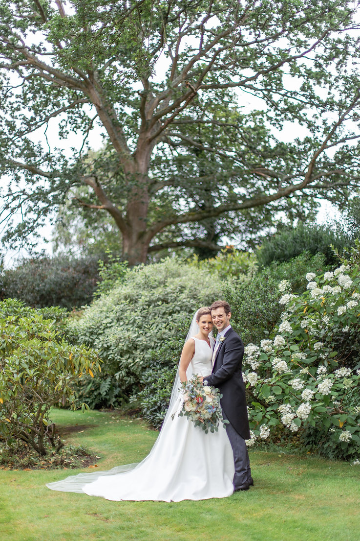 Bride and Groom posed portrait in natural sunlight and greenery wearing Jesus Peiro wedding dress from Miss Bush Bridal
