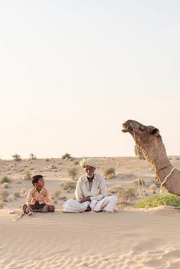 Indian man sitting with camel in Jaisalmer desert India