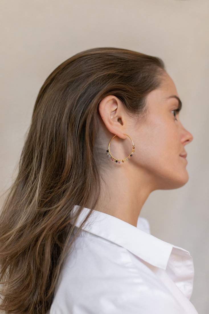 Model in white shirt wearing LuluB jewellery colourful hoop earrings
