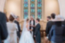 Bride and groom saying vows in English church
