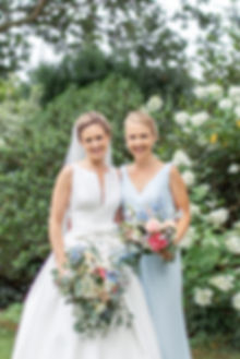 Bride and maid of honour smiling holding flower bouquets in wearing Jesus Peiro wedding dress