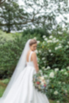 Bride holding flower bouquet wearing Jesus Peiro wedding dress from Miss Bush Bridal