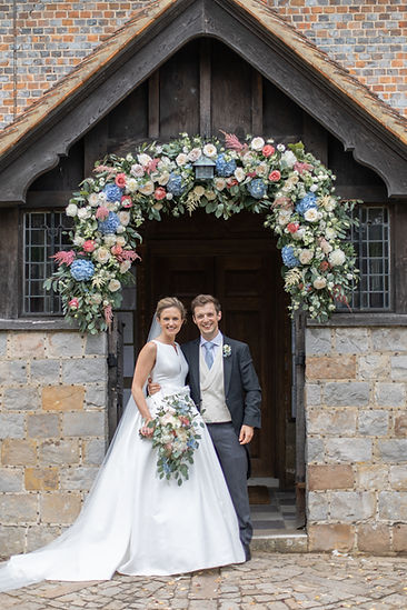 Bride and groom standing under flower arch at traditional English church wearing Jesus Peiro