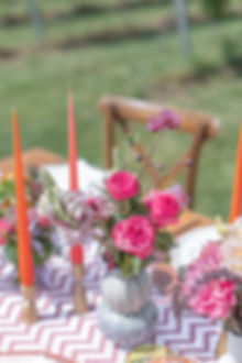 Light and bright pink flowers in vase with pink candlesticks for colourful styled tablescape shoot