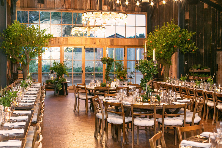 Tablescape of The Hay Barn at Soho Farmhouse with wooden chairs and chandeliers
