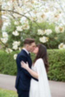 Bride and Groom kissing under blossom tree in Regent's Park luxury London wedding photographer