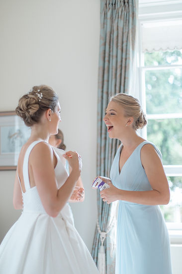 Bride and maid of honour laughing getting ready wedding day morning