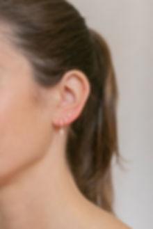Model wearing LuluB jewellery cross earrings