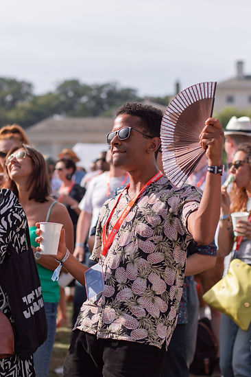 Man with fan dancing in crowds at Soho House Festival
