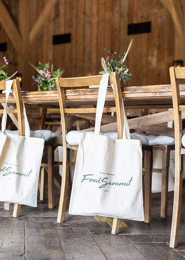 Cream tote bags on wooden chairs at event Soho Farmhouse
