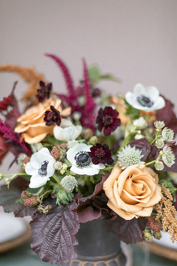 Orange white and maroon table flowers for autumnal winter tablescape inspiration