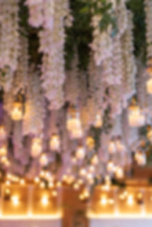 Solymar Mykonos Greek wedding dinner tablescape with rattan chairs and hanging lanterns floral installation
