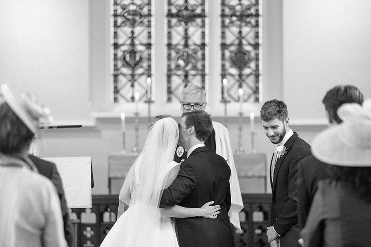 Groom kissing bride on cheek in English church during wedding ceremony