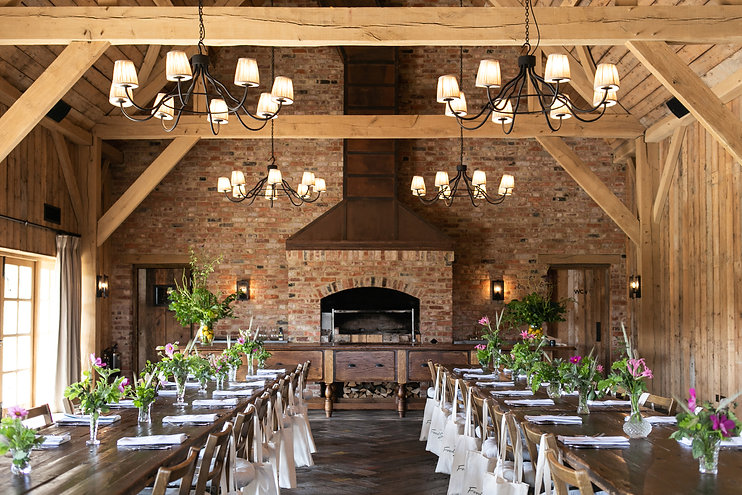 Long wooden tables event with in Barnwell Barn at Soho Farmhouse in Cotswolds Oxfordshire