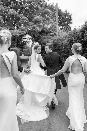 Bride and groom walking down road looking over shoulders bridesmaids holding wedding dress