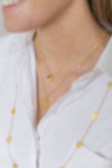 Model in white shirt wearing LuluB jewellery layered gold necklaces