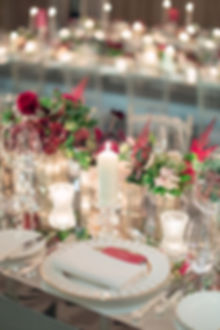 Candlelit mirrored tabletop tablescape with green and pink flowers at Claridges luxury event