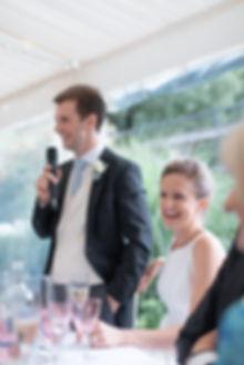 Bride smiling during grooms wedding speech