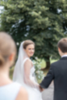 Bride looking over shoulder wearing Jesus Peiro wedding dress from Miss Bush Bridal