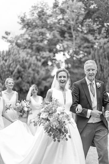 Bride in Jesus Peiro wedding dress from Miss Bush Bridal with father smiling walking into church