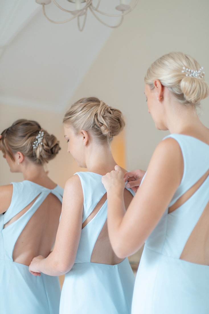 Bridesmaids getting ready in blue dresses and low bun