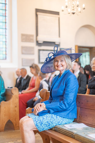 Mother of the bride smiling in English church during ceremony