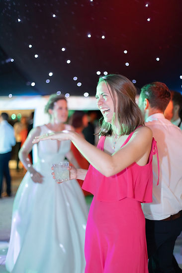 Woman in pink dress smiling and dancing on dancefloor