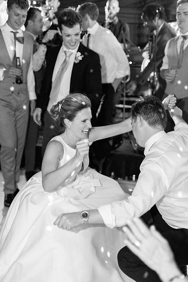 Bride dancing with guests at her English wedding on dancefloor