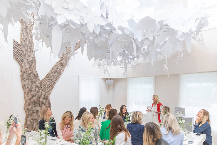 Carole Bamford speaking at Bamford Brompton Cross event with neutral green foliage and white flowers tablescape