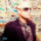 Blur image of Jéóh against a wall with glasses on
