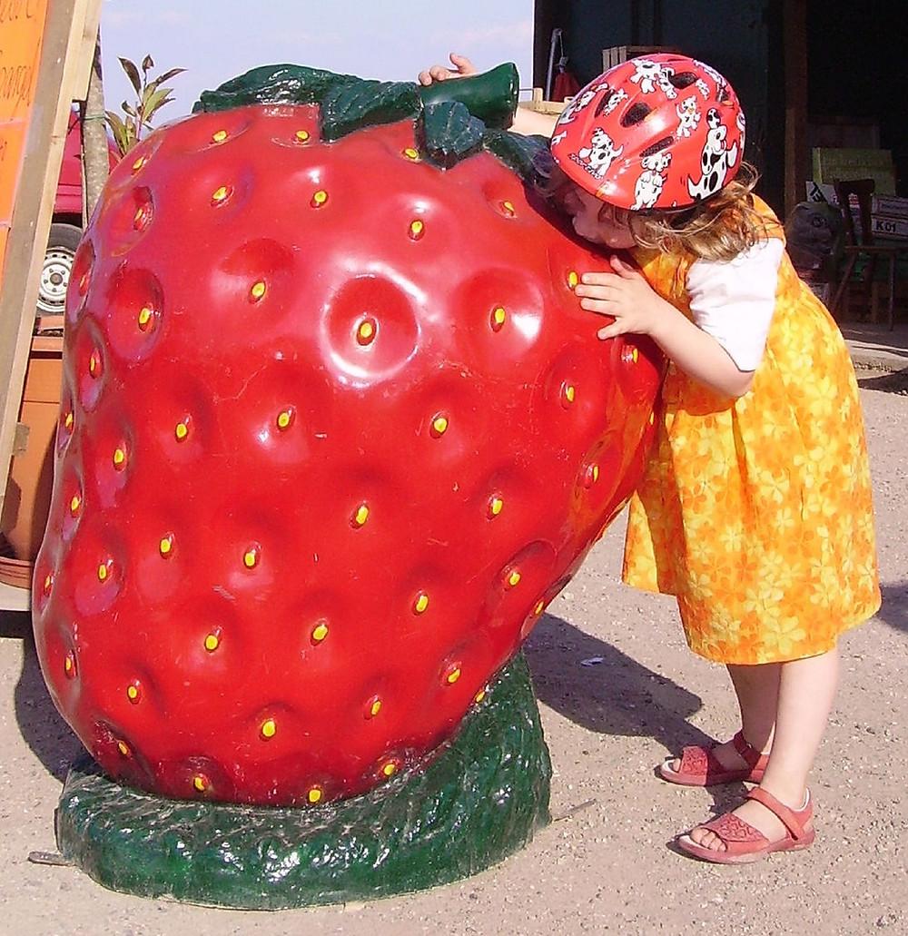 ילדה ליד פסל של תות שדה ענקי