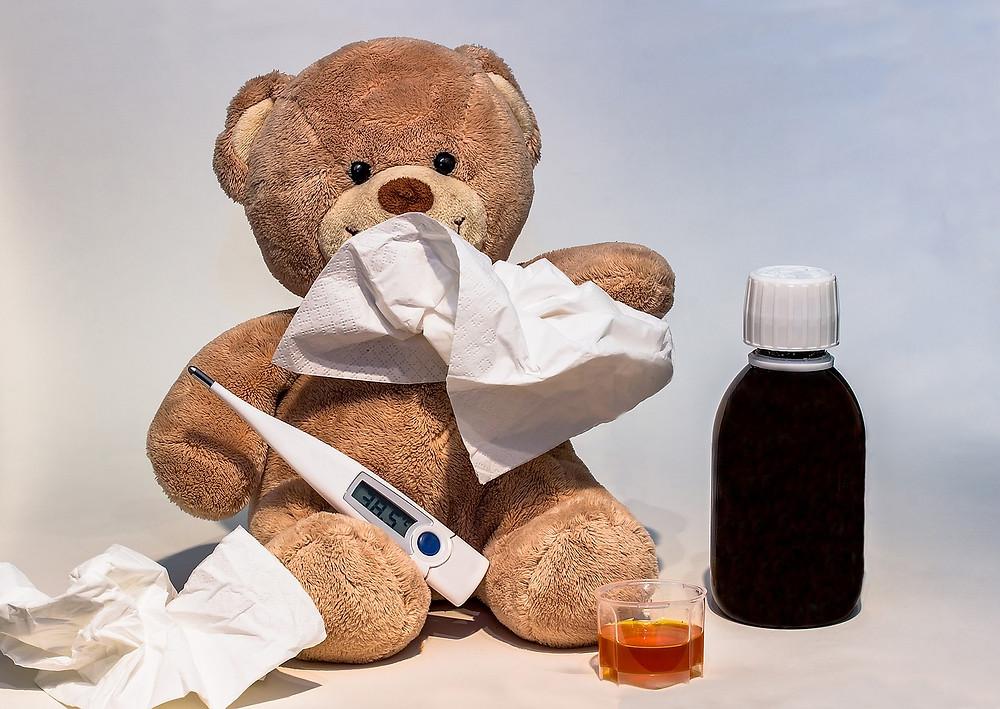 דובון עם מדחום, טישו ובקבוק של תרופה