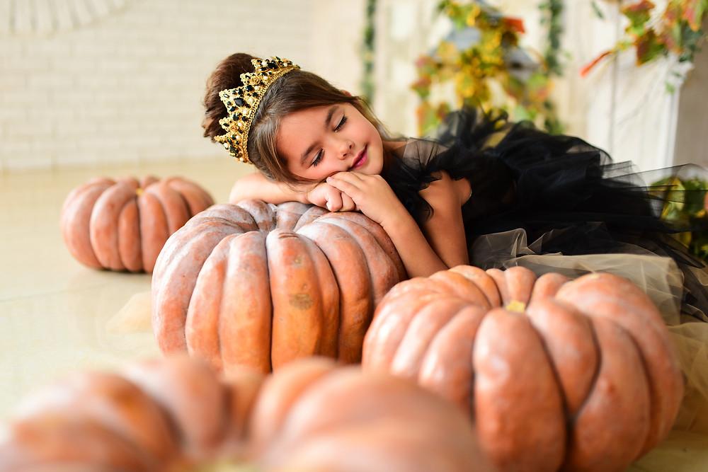 ילדה מחופשת לנסיכה מנמנמת על דלעת ענקית