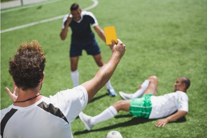 שופט כדורגל מניף כרטיס צהוב