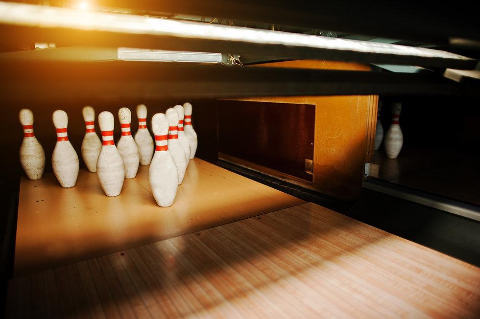 Ten white pins in a bowling alley lane.j