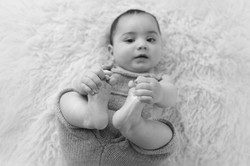 close up baby holding feet