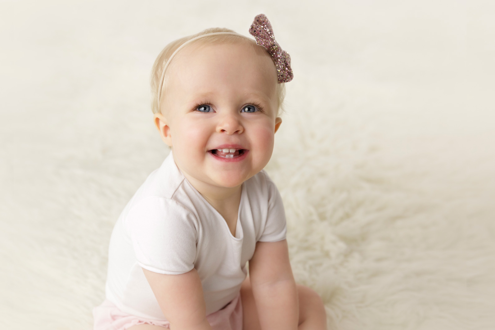 smiling one year old showing teeth