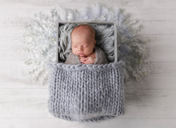 newborn boy in crate prop