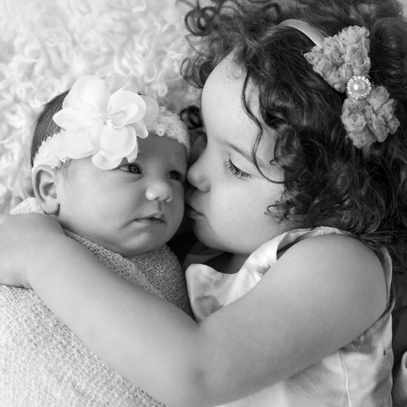 sister kissing baby sister