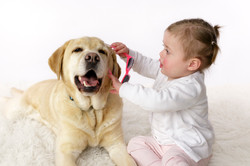 baby playing dress up with dog