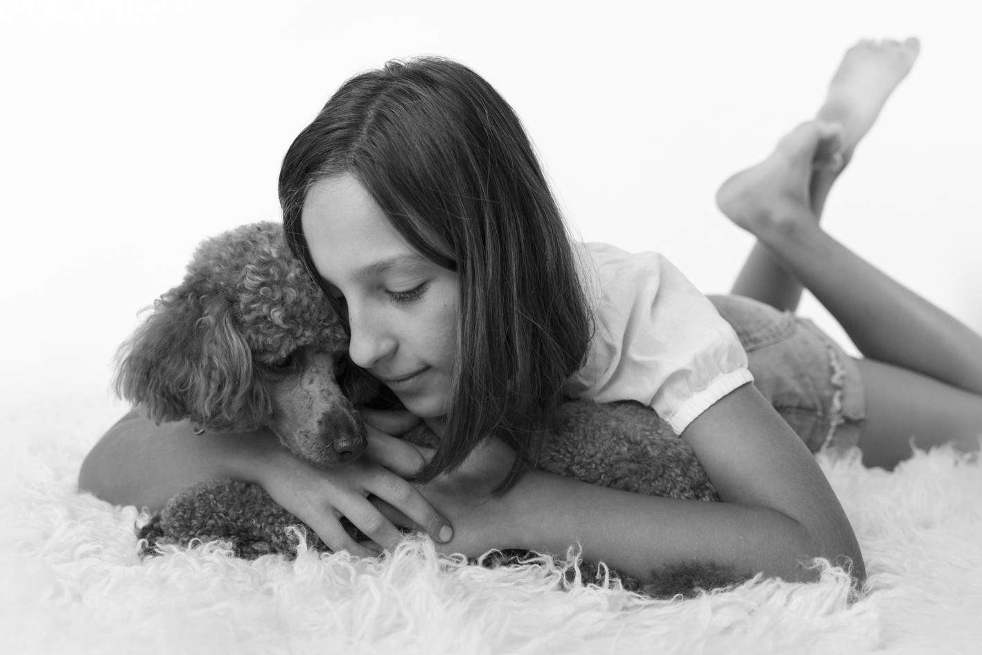 child cuddling dog black and white