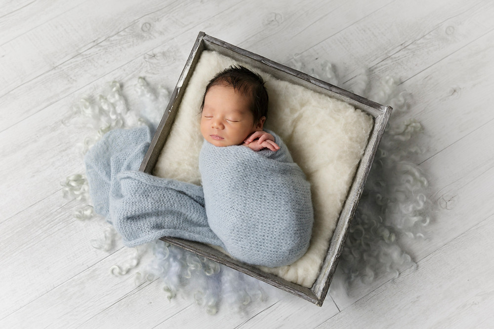 newborn baby boy in basket prop