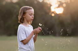 young girl blowing flower
