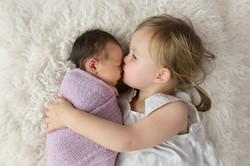 sister kissing baby