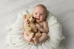 baby boy cuddling teddy