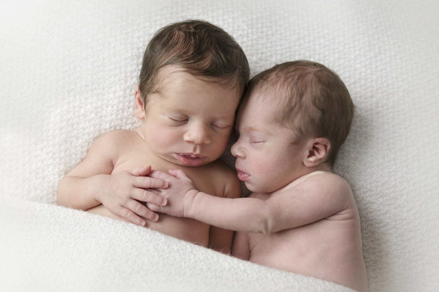 newborn twin girls hugging